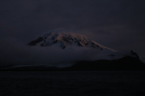 Big Ben seen in twilight from Atlas Cove.  On unusually clear nights such as this one, the summit of the volcano can be seen from sea level.  Under ordinary circumstances, the low clouds would be too thick to see up more than 1000-2000 feet.  Image credit: Bill Mitchell (CC-BY).