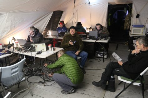 Inside the operating tent are many tables with radio equipment.  We have six stations set up, two of which are outside the frame to the left.  The galley is just barely showing on the right, and I'm standing in the front door.  The sleeping tent is through a little hallway.  From left to right, by leftmost extent of the head, we have Adam, Dave Lloyd, Jim, Vadym, Ken, Arliss, and Hans-Peter.  Image credit: Bill Mitchell (CC-BY)