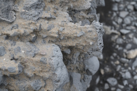 Close-up, oblique view of the outcrop face.  Here the differential weathering (resistant grey clasts, weak tan matrix) is very apparent.  Spires of matrix are left to the leeward of the clasts, and are roughly horizontal. Image credit: Bill Mitchell (CC-BY).