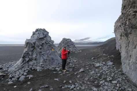 Looking eastward at Windy City, with a person for scale. The gigapanned portion of the outcrop is at right, but two spires of similarly eroded rock outcrop further to the north of the photographed portion. The stake coming out from the outcrop is a marker for one of our temperature/light intensity sensors. Image credit: Carlos Nascimento