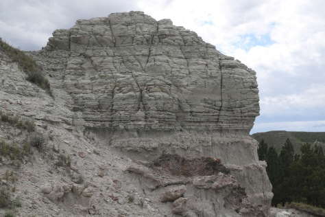 Contact between spheroidally-weathered strata (above) and easily-weathered basal unit (below).  Possible channel cut at right.  Outcrop height in image is ~10 m.  Image credit: Bill Mitchell (CC-BY).
